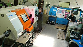 two employees working with CNC machine